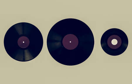 Vintage looking Size comparison of many analogue recording media for music. Left to right: shellac record 78 rpm, vinyl record 33 rpm and 45 rpm - purple label Stock Photo