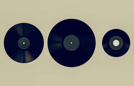 Vintage looking Size comparison of many analogue recording media for music. Left to right: shellac record 78 rpm, vinyl record 33 rpm and 45 rpm