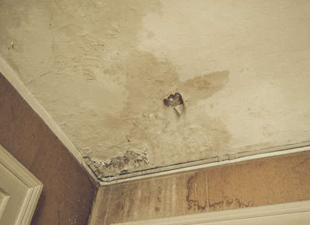 damp: Vintage looking Damage caused by damp and moisture on a ceiling Stock Photo