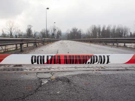 deluge: Local Police line (Polizia Municipale in Italian), do not cross. Bridge access blocked for flood risk Stock Photo