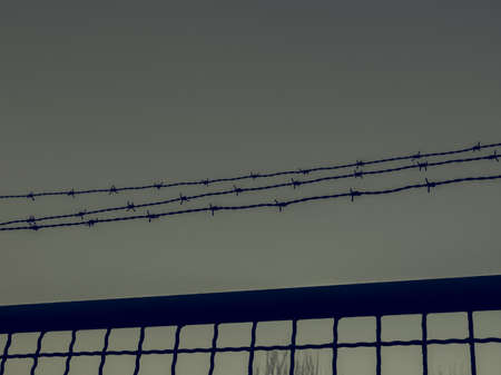 trespass: Vintage looking Detail of a barbed wire fence protection