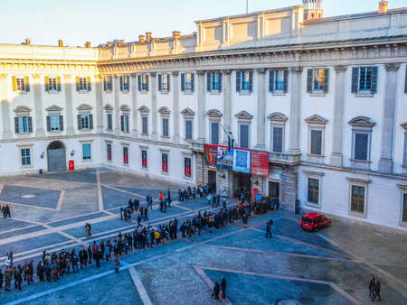 queueing: MILAN, ITALY - FEBRUARY 23, 2014: People queueing in front of Palazzo Reale exhibition room to visit a temporary exhibition (HDR)