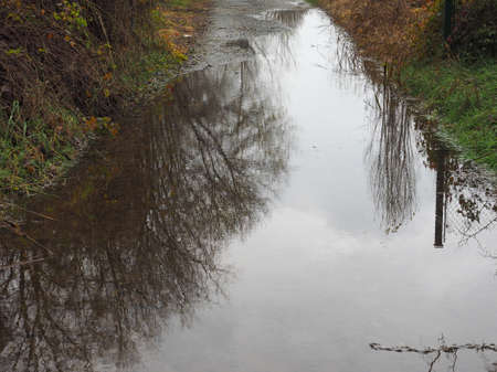 Pond in a country street caused by heavy rain and river flood Stock Photo
