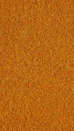pasto sintetico: Orange artificial synthetic grass meadow useful as a background - vertical