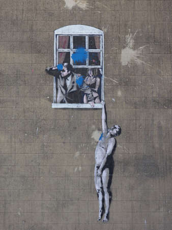 adultery: BRISTOL, UK - CIRCA SEPTEMBER 2016: Well Hung Lover graffiti by artist Banksy has been vandalised with blue paint