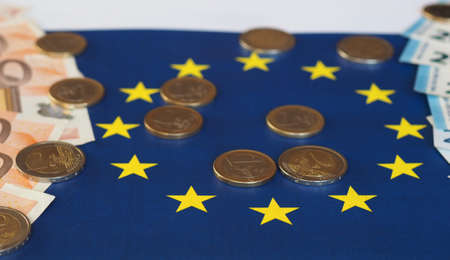 Euro banknotes and coins (EUR), currency of European Union over flag of Europe