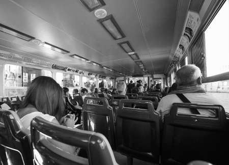waterbus: VENICE, ITALY - CIRCA SEPTEMBER 2016: Travellers on a vaporetto (meaning waterbus) public transport in black and white