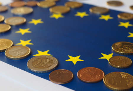 Euro coins (EUR), currency of European Union over flag of Europe Stock Photo