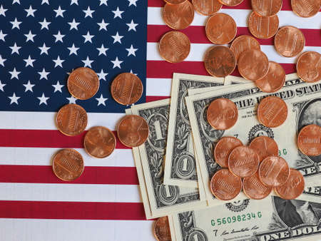 One Dollar banknotes and One Cent coins (USD) currency money over the flag of the United States