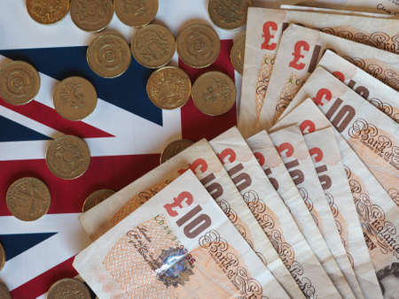 earn money: Pound coins and banknotes money (GBP), currency of United Kingdom, over the Union Jack Stock Photo
