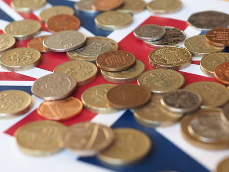 Pound coins money (GBP), currency of United Kingdom, over the Union Jack Stock Photo
