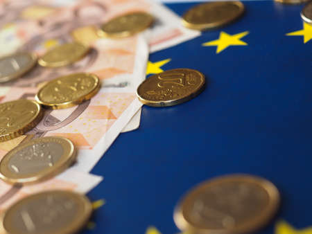 earn money: Euro banknotes and coins (EUR), currency of European Union over flag of Europe