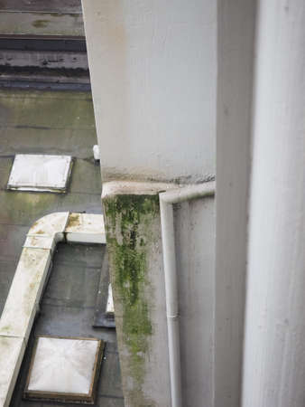 humid: damage caused by damp and moisture on a wall and flat roof Stock Photo