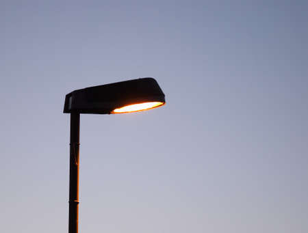 street lamp: street light lit lamppost at night over blue sky with copy space over blue sky