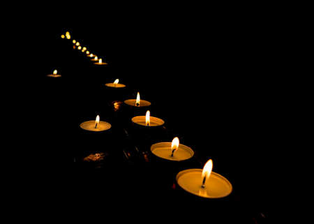 flickering flame of lit votive prayer wax candles in a church shining in the dark Фото со стока