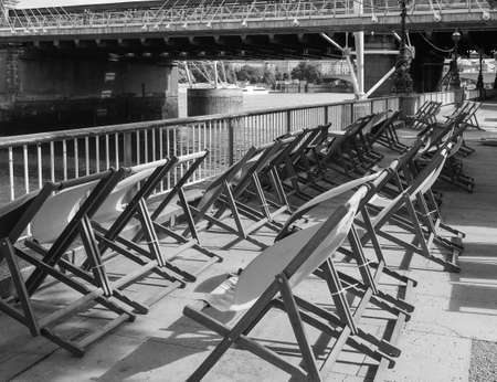 LONDON, UK - CIRCA JUNE 2017: Deckchairs on the bank of River Thames in black and white Editorial