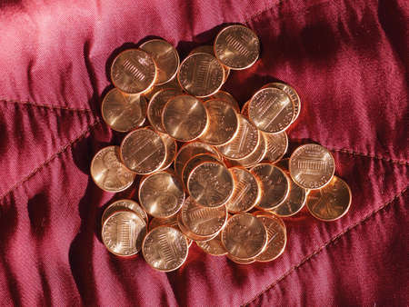 One Cent Dollar coins money (USD), currency of United States over crimson red velvet background