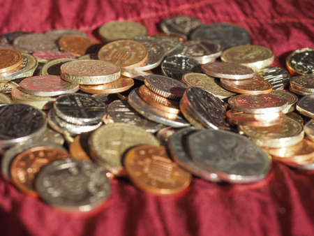 Pound coins money (GBP), currency of United Kingdom over crimson red velvet background Stock Photo