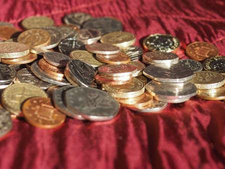 Pound coins money (GBP), currency of United Kingdom over crimson red velvet background 版權商用圖片