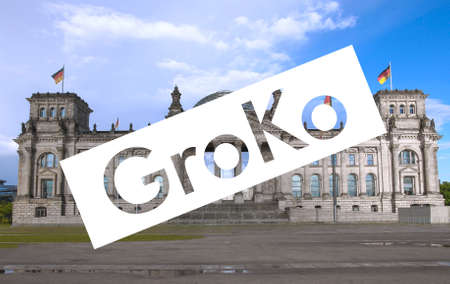 GroKo (short for Grosse Koalition, meaning Large Coalition) superimposed to the Reichstag houses of parliament in Berlin, Germany
