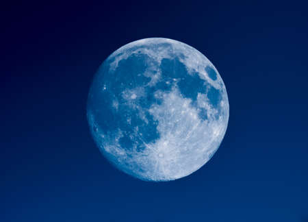 High contrast Full moon seen with an astronomical telescope over blue sky