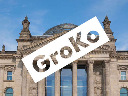 GroKo (short for Grosse Koalition, meaning Grand Coalition) superimposed to the Reichstag houses of parliament in Berlin, Germany
