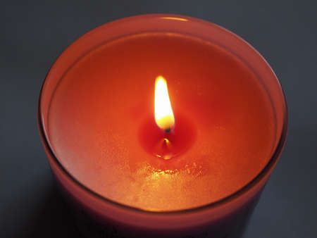red lit scented candle with flickering flame