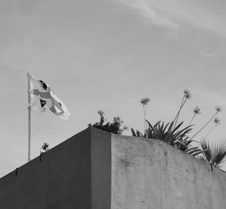 flag of Sardinia (aka flag of the Four Moors) on the top of a wall, over blue sky in black and white 写真素材
