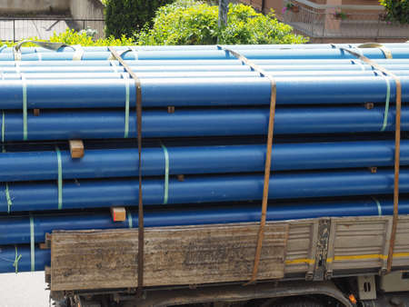large blue pipes being transported on a truck