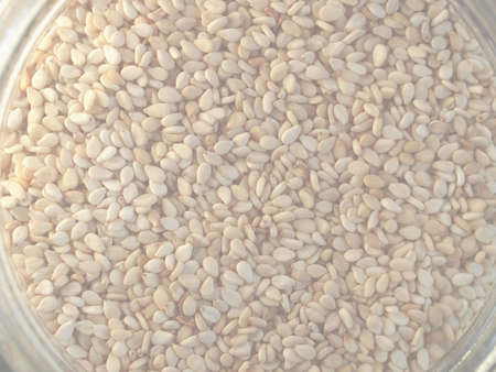 A heap of brown yellow sesame seeds, delicate soft faded tone useful as background 版權商用圖片
