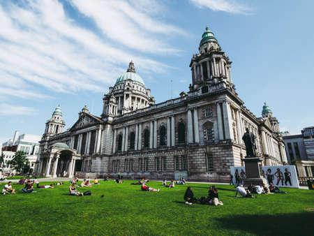 BELFAST, UK - CIRCA JUNE 2018: People in the park in front of Belfast City Hall Editorial