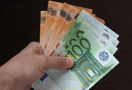 Hand hält und gibt Euro-Banknoten Geld (EUR), Währung der Europäischen Union