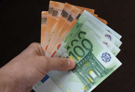 Hand holding and giving Euro banknotes money (EUR), currency of European Union 스톡 콘텐츠 - 110749756