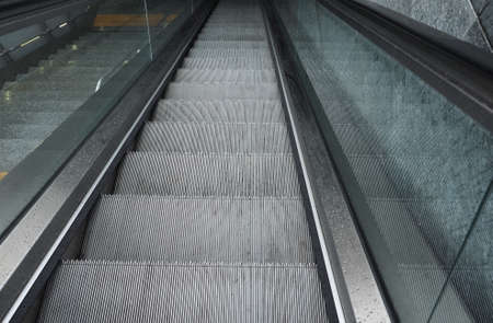 Escalator moving staircase to carry people between floors of a building
