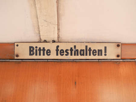 Bitte festhalten (meaning Please hold tight) sign on vintage German tram