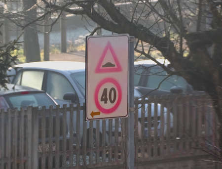 speed bump (aka as speed hump or sleeping policeman) to limit speed of cars traffic sign