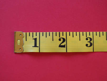 a ruler with Imperial units, over red background