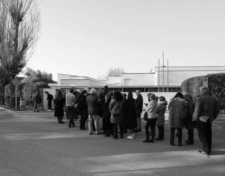 ALBA, ITALY - CIRCA FEBRUARY 2019: People queueing to visit an exhibition at Fondazione Ferrero art gallery in black and white