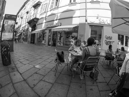 TURIN, ITALY - CIRCA SEPTEMBER 2018: People in the city centre in Via Garibaldi, view with fisheye lens in black and white