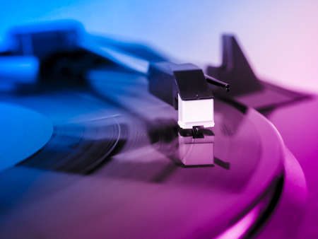 Vinyl record spinning on a turntable, focus on needle - pink and blue light