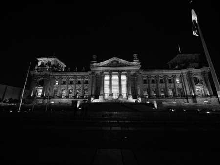 Bundestag German Houses of Parliament in Berlin, Germany at night. Dem deutschen Volke means To the German people in black and white Banco de Imagens