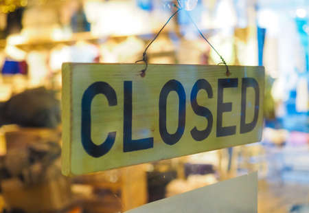Closed sign in a shop showroom with selective focus and blurred background