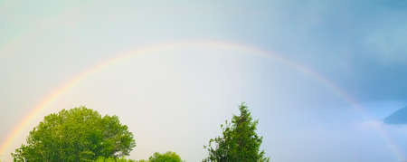 rainbow caused by reflection, refraction and dispersion of sun light in rain water droplets, resulting in spectrum of light in the sky in the form of a multicoloured circular arc