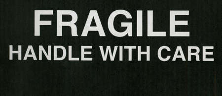Fragile handle with care warning sign in white over black