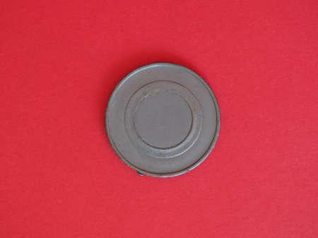 Grey plastic chip fiche token money - over red background