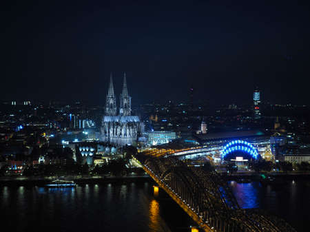 Night aerial view Koelner Dom Sankt Petrus (meaning St Peter Cathedral) gothic church and Hohenzollernbruecke (meaning Hohenzollern Bridge) crossing the river Rhein in Koeln, Germany