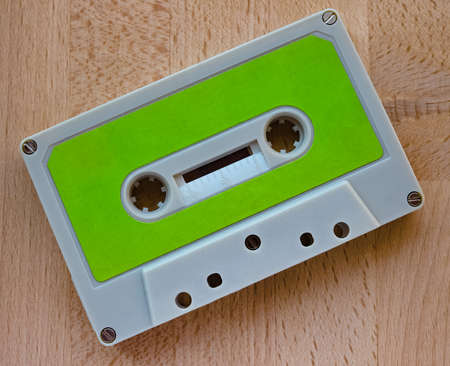 Magnetic tape cassette for analog audio music recording on a wooden table