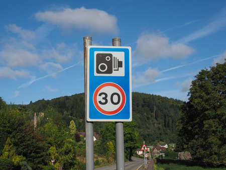 Speed camera sign, with 30 kmph or 30 mph