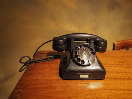 vintage black analog rotary dial telephone on a desk
