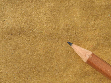 wooden pencil on blank brown paper with copy space